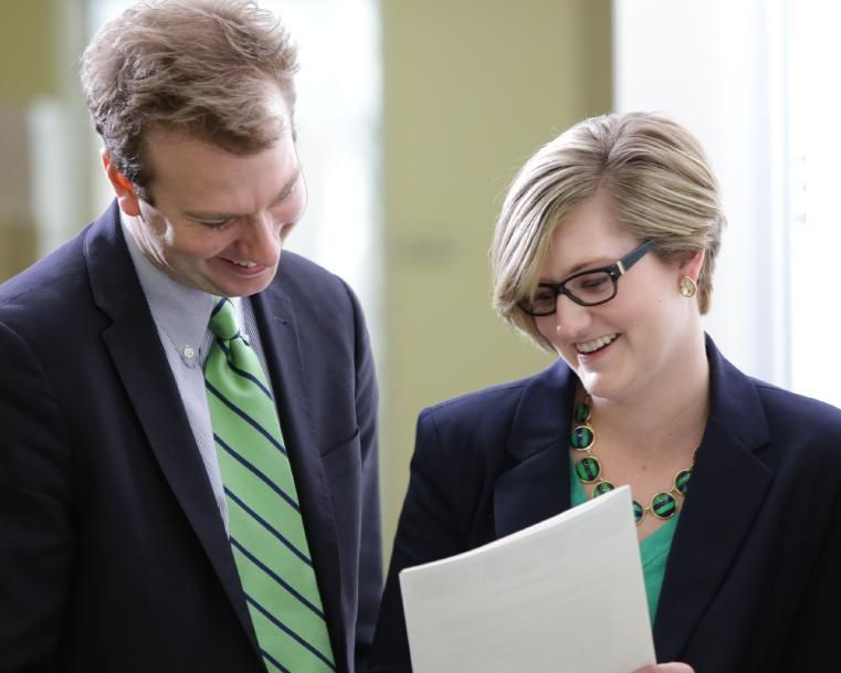 Two associates looking at a paper.