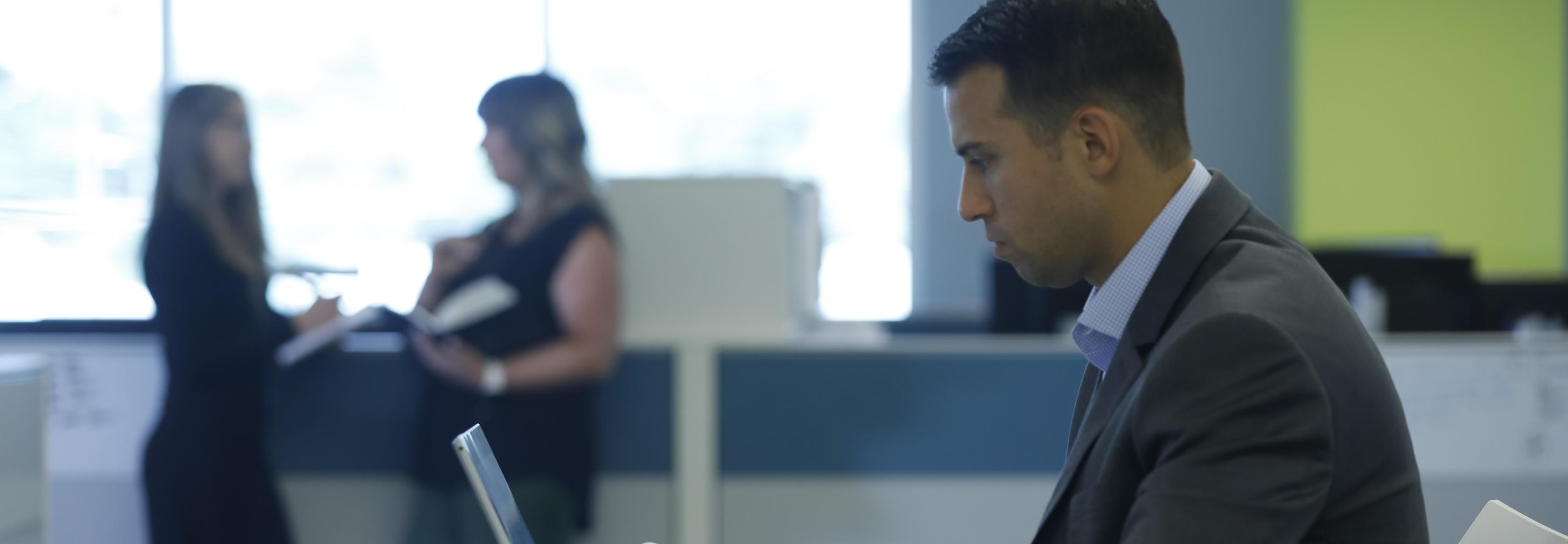 Associate working on a laptop.